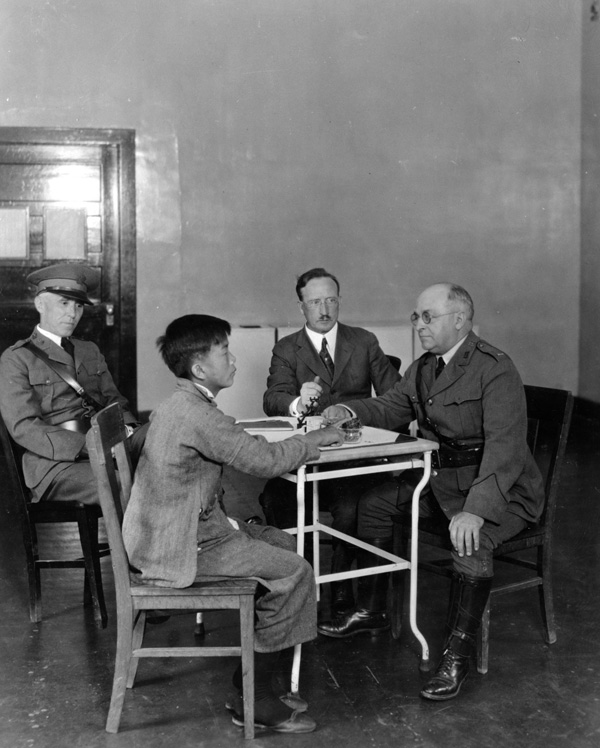 <strong><em>A Chinese immigrant is interrogated by US immigration inspectors on Angel Island</em></strong><strong>, 1923. National Archives, College Park, MD (90-G-124-479).</strong>